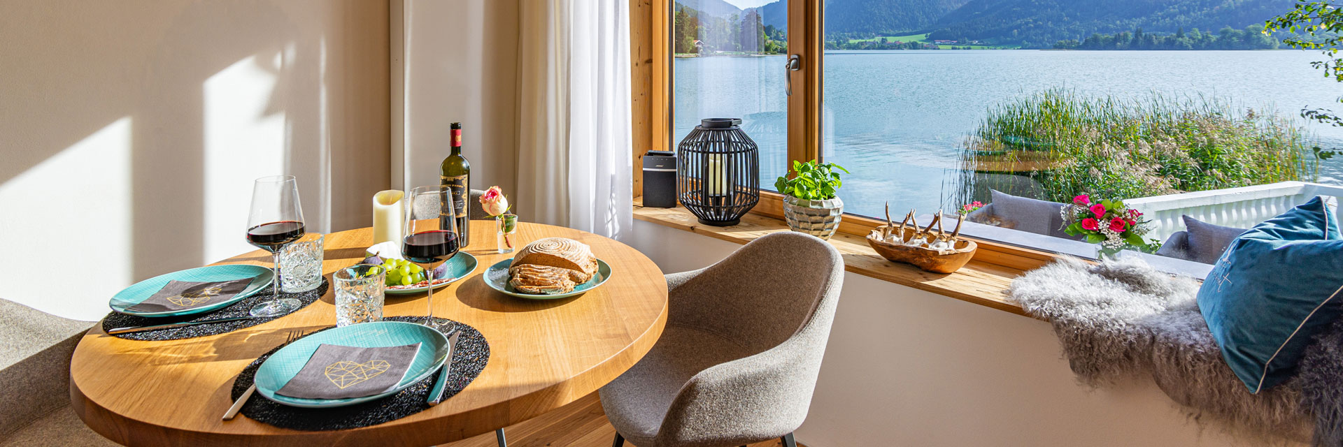 Seeheimat Wohnzimmer mit Abendessen und Blick auf den Schliersee